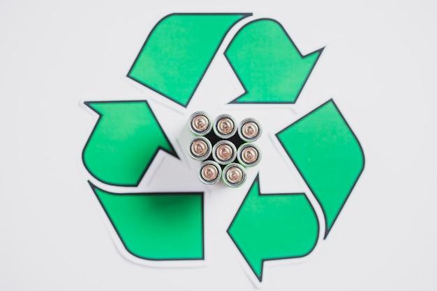 Una vista aérea de las baterías en el icono de reciclaje sobre fondo blanco