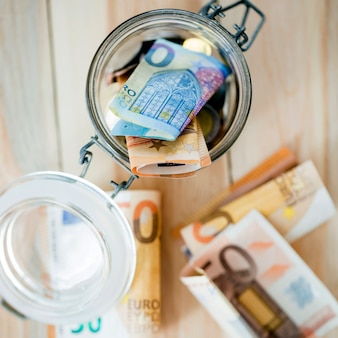 Una vista aérea de los billetes en euros en un frasco de vidrio abierto