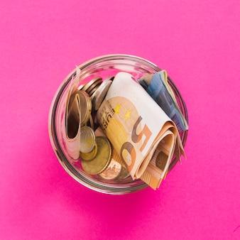 Una vista aérea de billetes y monedas en euros en frasco de vidrio abierto sobre fondo rosa