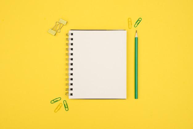 Vista aérea del bloc de notas espiral en blanco con lápiz y clip sobre superficie amarilla