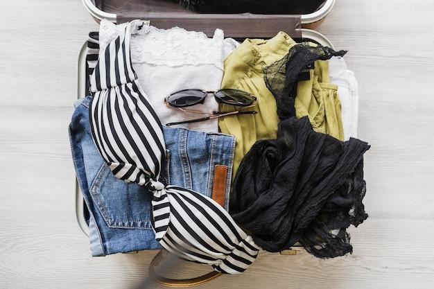Vista aérea de la bolsa de viaje abierta con trajes y accesorios
