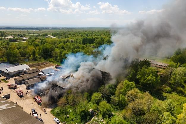 Vista aérea de los bomberos extinguiendo el edificio en ruinas en llamas con techo derrumbado y humo oscuro ascendente.