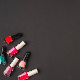 Vista aérea de botellas de esmaltes de uñas de varios colores en superficie negra