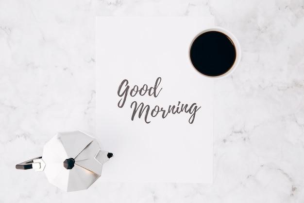 Vista aérea de una cafetera italiana de aluminio y una taza de café sobre papel con texto de buena mañana