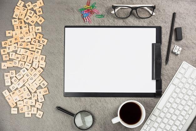 Una vista aérea de la caja de madera del alfabeto con suministros de oficina y una taza de café en el escritorio