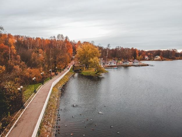 Vista aérea caminando camino a lo largo del lago, bosque colorido del otoño. san petersburgo, rusia.