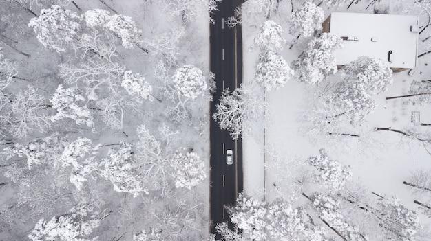 Vista aérea del camino cubierto de nieve en el bosque de invierno, camión pasando, desenfoque de movimiento