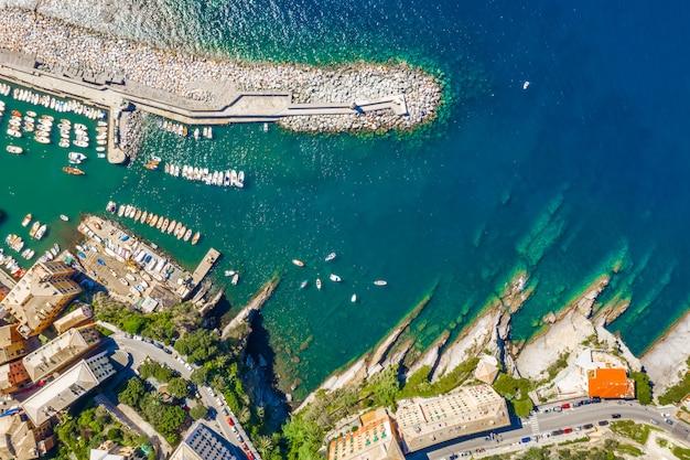 Vista aérea de camogli marina. barcos y yates amarrados en el puerto con agua verde y faro.