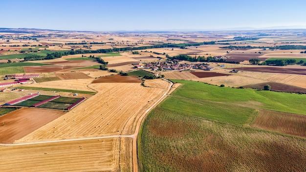 Vista aérea de campos agrícolas y pueblo rural al fondo. segovia.