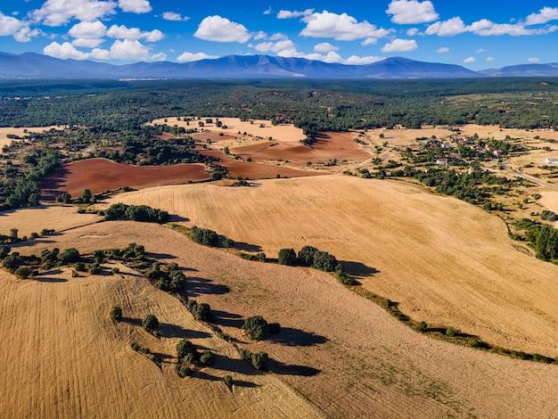 Vista aérea de campos de cultivo con cielo azul y montañas de fondo. segovia.