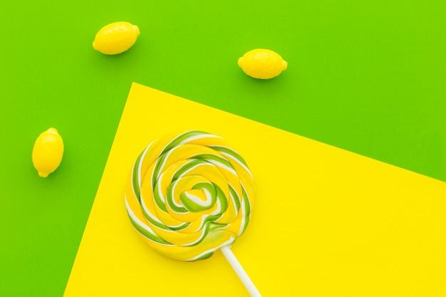 Vista aérea de caramelos de lollipop y limón sobre fondo multicolor