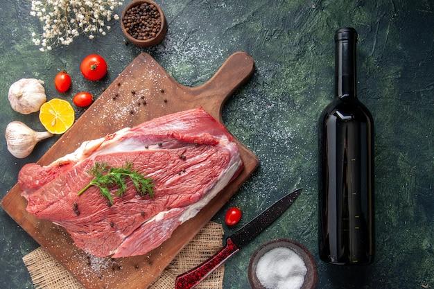 Vista aérea de la carne roja cruda fresca sobre una tabla de cortar de madera en una toalla de color nude, una botella de vino de flores de ajo y limón sobre fondo de colores mezclados