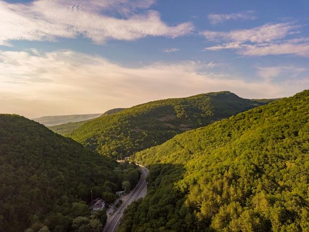 Vista aérea de la carretera ancha entre las montañas cubiertas de bosques verdes