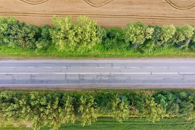 Vista aérea de una carretera entre campos de trigo amarillo y árboles verdes.