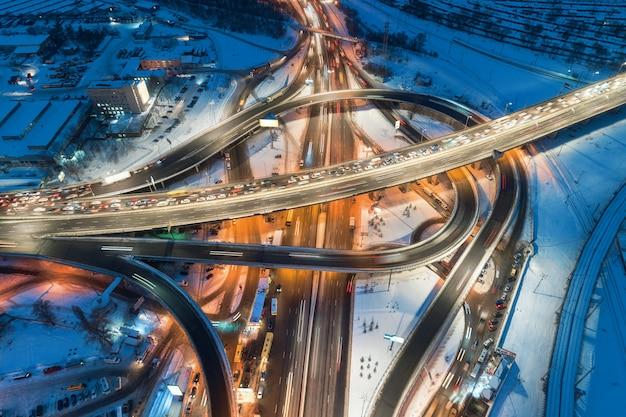 Vista aérea de la carretera en la ciudad moderna por la noche en invierno. vista superior del tráfico en el cruce de la autopista con iluminación.