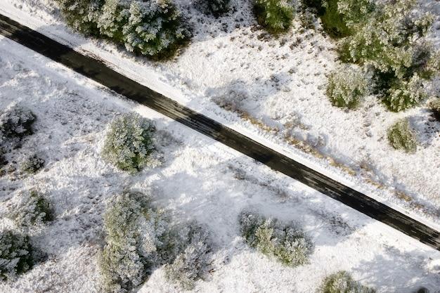Vista aérea de la carretera cubierta de nieve vacía en el bosque de invierno.