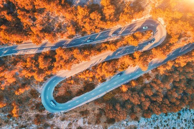 Vista aérea de la carretera curva de montaña con coches, bosque de naranja al atardecer en otoño
