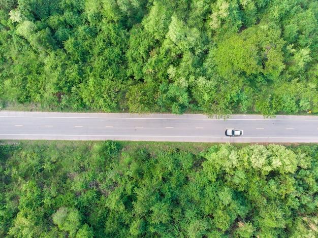 Vista aérea de la carretera pasando por el bosque con un automóvil pasando por