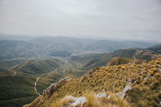 Vista aérea de una carretera rural pasando por los árboles y las montañas