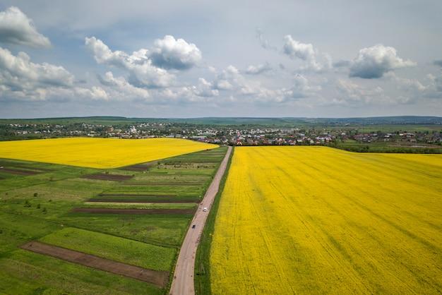 Vista aérea de la carretera de tierra con coches en movimiento en campos verdes con plantas de colza en flor, casas de los suburbios en el horizonte y espacio de copia de cielo azul. fotografía de drones.