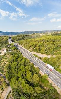 Vista aérea de la carretera de varios carriles que cruza pueblos y colinas forestales (autostrada dei fiori - a10) liguria italia