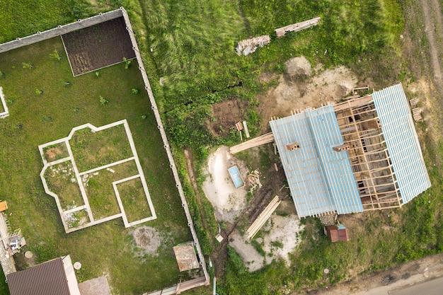 Vista aérea de una casa de ladrillos con techo de madera en construcción y cimientos para un nuevo proyecto.