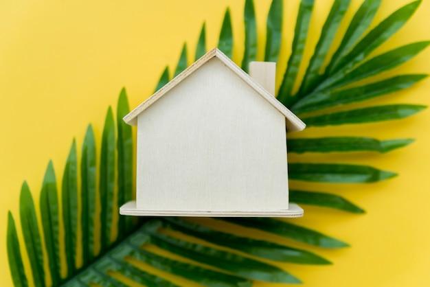 Una vista aérea de la casa de madera sobre las hojas verdes sobre fondo amarillo