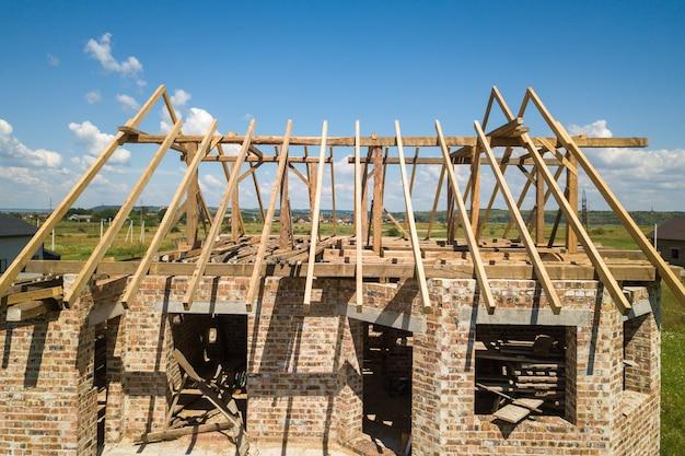 Vista aérea de la casa sin terminar con estructura de techo de madera en construcción.