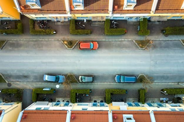 Vista aérea de casas residenciales con techos rojos y calles con autos estacionados en la zona de la ciudad rural