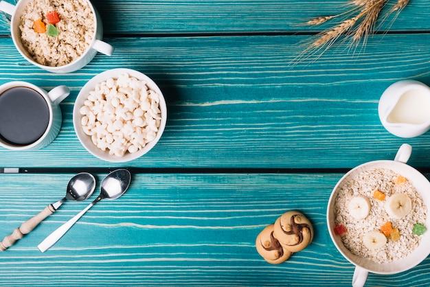 Vista aérea de cereales, avena con café y té en la mesa de color turquesa