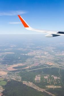 Vista aérea del cielo azul de la nube y de la vista del ala plana a través de la ventana del avión.