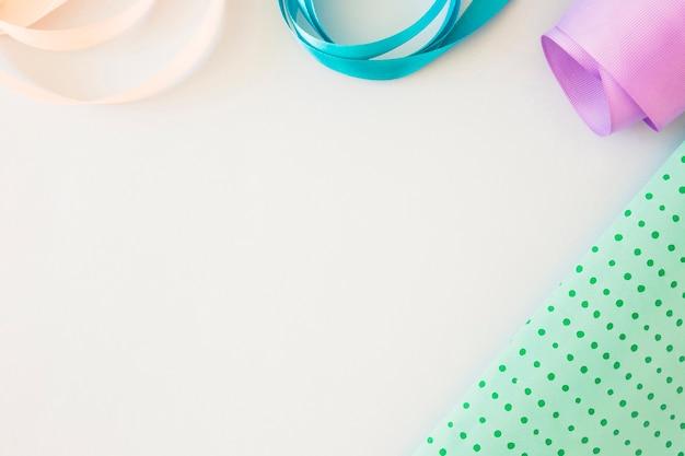 Vista aérea de cintas de raso rizadas y papel de regalo sobre fondo blanco