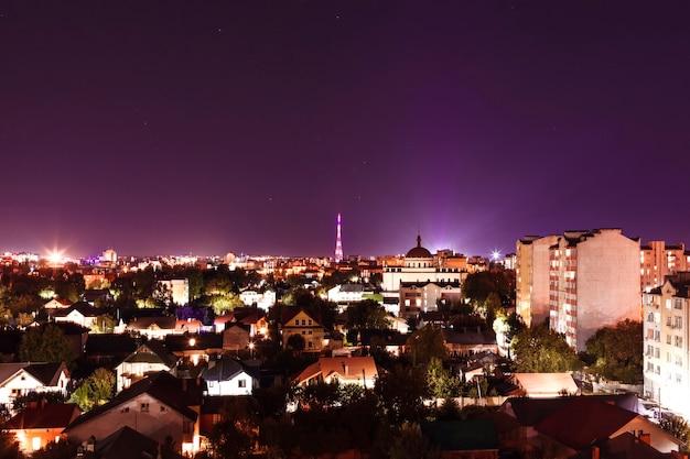 Vista aérea de la ciudad iluminada por la noche con casas privadas e iglesia