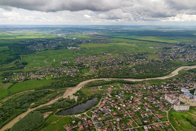 Vista aérea de la ciudad o pueblo con hileras de edificios y calles curvas entre campos verdes en verano. paisaje de campo desde arriba.