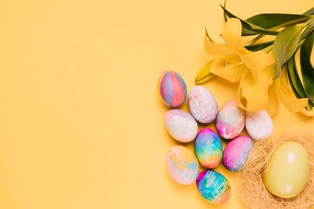 Una vista aérea de coloridos huevos de pascua con una hermosa flor de lirio sobre fondo amarillo