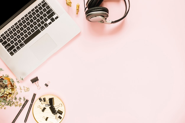Vista aérea de una computadora portátil abierta sobre fondo rosa