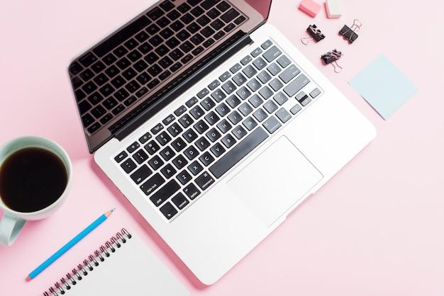 Una vista aérea de una computadora portátil abierta; taza de café; lápiz; bloc de notas y clip sobre fondo rosa