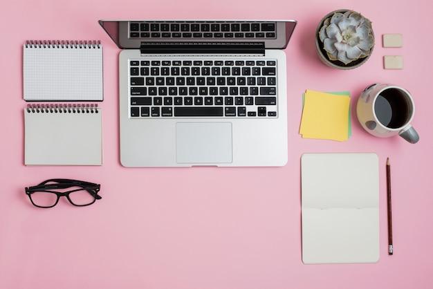 Una vista aérea de la computadora portátil; bloc; los anteojos; notas adhesivas; planta de cactus y taza de té sobre fondo rosa