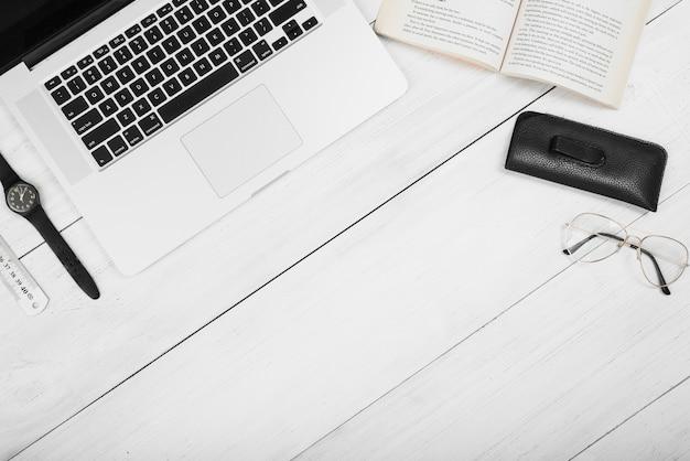 Una vista aérea de la computadora portátil con el libro; los anteojos; regla y reloj de pulsera en mesa de madera blanca.
