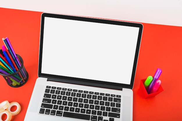 Vista aérea de una computadora portátil que muestra una pantalla blanca con papelería de colores en un escritorio rojo