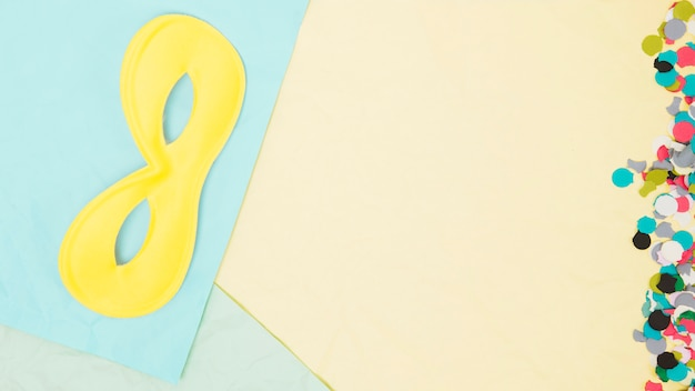 Vista aérea de confeti colorido y máscara de ojo amarillo y papeles