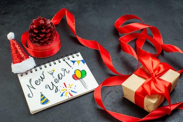 Vista aérea de un cono de coníferas de regalo con cinta roja y cuaderno con escritura de año nuevo y sombrero de santa claus hermoso regalo sobre fondo oscuro