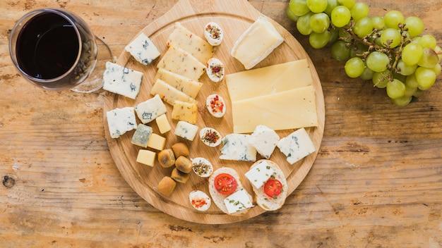 Una vista aérea de copa de vino tinto con bloques de queso y tomates en el escritorio de madera