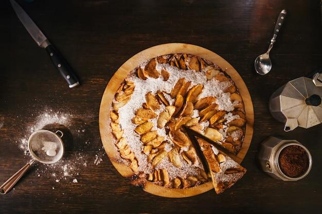 Vista aérea de cortar tarta de manzana casera y cafetera moka en rústica mesa de madera oscura con espacio de copia