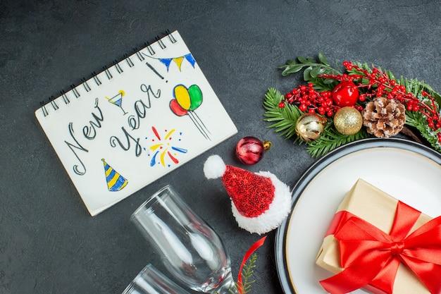 Vista aérea del cuaderno con año nuevo escribiendo en plato de cena árbol de navidad ramas de abeto cono de coníferas sombrero de santa claus copas de vidrio caído sobre fondo negro