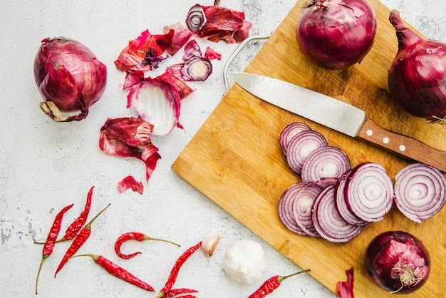 Vista aérea de cuchillo; rodajas de cebolla en tabla de cortar con chiles rojos y ajo
