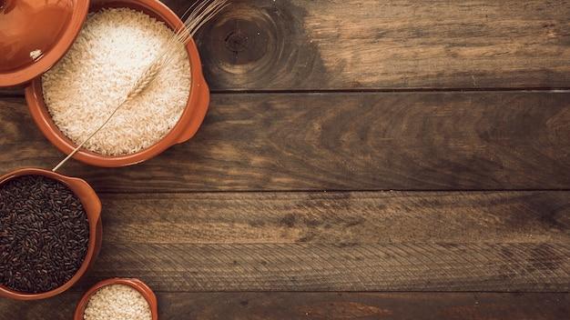 Vista aérea de cuencos de grano de arroz saludable en la mesa de madera