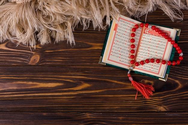 Vista aérea de cuentas de oración con libro sagrado islámico en escritorio de madera