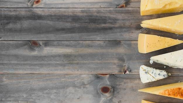 Vista aérea de cuñas de queso triangulares en mesa de madera