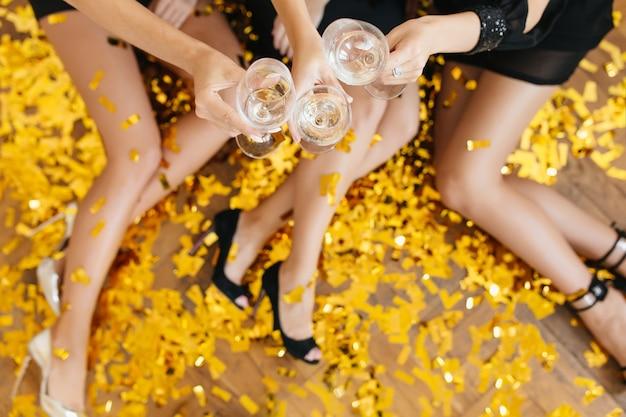 Vista aérea de damas divirtiéndose en fest y tintinear copas